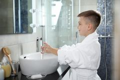 Little boy washing hands with soap. In bathroom royalty free stock image