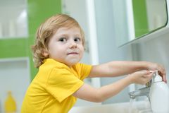 Little boy washing his hands in the bathroom stock image