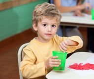 Little Boy Washing Paintbrush In Glass. Portrait of little boy washing paintbrush in glass at classroom desk Royalty Free Stock Image