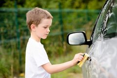 Little boy washing silver car in the garden Stock Photography