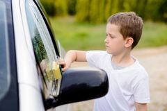Little boy washing silver car in the garden Royalty Free Stock Image