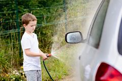 Little boy washing silver car in the garden Stock Image