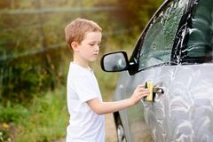 Little boy washing silver car in the garden Royalty Free Stock Photography