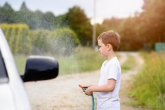 Little boy washing silver car in the garden Royalty Free Stock Images