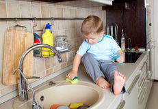 Little boy washing sink on kitchen Royalty Free Stock Photo