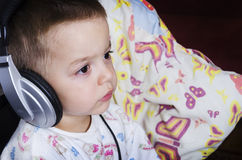 Little boy watching cartoons before bedtime. Little boy watching cartoons or listening music before bedtime. A boy holding his favorite pillow Stock Photos