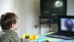 Little boy watching cartoons at laptop and eating apples, stock footage Royalty Free Stock Image