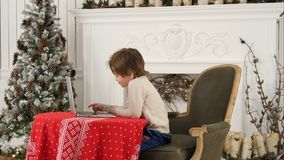 Little boy watching Christmas movie on a laptop at home stock image