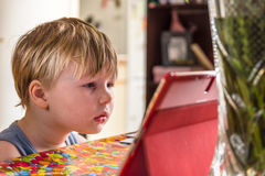 Little Boy watching digital tablet with face expression.  royalty free stock photo