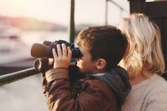 Little boy watching into distantance by binoculars with mother i. Little caucasian boy watching, gazing, looking, searching for by binoculars with mother in Stock Photo