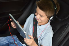 Little boy watching film on tablet while driving in the car Stock Images