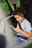 Little boy watching film on tablet driving in car. Kid watching moving on tablet inside car Stock Photo