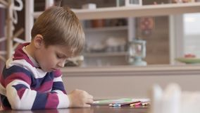 Little boy watching a funny cartoon on a smartphone. While sitting at the table on cozy cafe stock video footage
