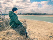 Little boy watching high tide coming. Little boy  sitting at the dune, looking the high tide coming, north sea, Dutch coast near Cadzand. Vintage filter used Stock Images