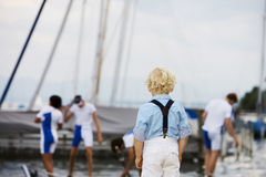 Little boy watching his favourite sports team. Little boy with curly blonde hair standing with his back to the camera watching his favourite sports team Stock Image