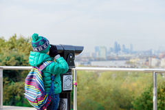 Little boy is watching London City through the stand binoculars Stock Image