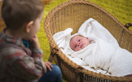 Little boy watching over his new born baby sister in the house Stock Image