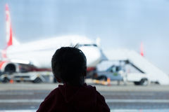 Little boy watching planes at the airport. Standing in silhouette with his back to the camera at a large window overlooking the tarmac Stock Photos
