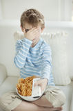 Little boy watching scary movie with a bowl full of wheel shape snack pellets Royalty Free Stock Photo