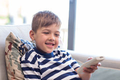 Little boy watching tv on the couch. At home in the living room Stock Photography