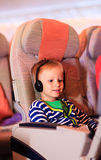 Little boy watching tv in flight, kids travel. Concept Royalty Free Stock Photos