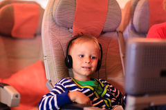 Little boy watching tv in flight, kids travel. Concept Stock Photos