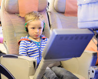 Little boy watching tv in flight. Travel concept Stock Image