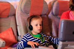 Little boy watching tv in flight, travel concept Stock Images