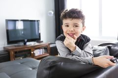 Little boy watching TV lying in the living-room. A little boy watching TV lying in the living-room Royalty Free Stock Image