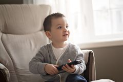 Little boy is watching tv while sitting on a couch. A Little boy is watching tv while sitting on a couch Stock Images