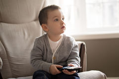 Little boy is watching tv while sitting on a couch. A Little boy is watching tv while sitting on a couch Royalty Free Stock Images