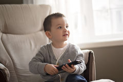 Little boy is watching tv while sitting on a couch. A Little boy is watching tv while sitting on a couch Stock Image