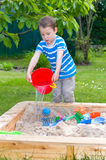 Little boy with water bucket in the sandbox Royalty Free Stock Photos