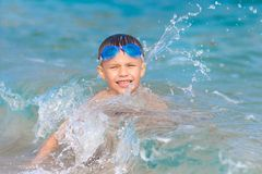 Little boy with water glasses swims in sea royalty free stock image