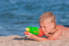 Little boy with water gun. Little boy play with water gun on a sand beach Stock Image