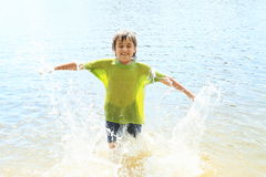 Little boy in water. Little boy - kid in wet clothes splashing the water Royalty Free Stock Images