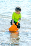 Little boy in water with orange bucket royalty free stock image