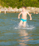 LIttle boy in water. Little boy running in the water at the seaside of Montenegro, during summer holidays Stock Photography