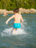 LIttle boy in water. Little boy running in the water at the seaside of Montenegro, during summer holidays Royalty Free Stock Image