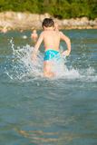LIttle boy in water. Little boy running in the water at the seaside of Montenegro, during summer holidays Stock Photos