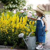 Little boy with watering can in summer park Royalty Free Stock Photography