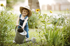 Little boy with watering can in summer park Royalty Free Stock Image