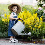 Little boy with watering can in summer park royalty free stock images