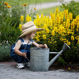 Little boy with watering can in summer park stock photography