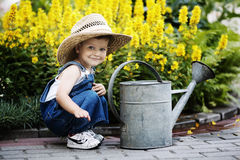 Little boy with watering can in summer park royalty free stock photos