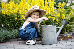 Little boy with watering can in summer park royalty free stock photo