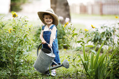 Little boy with watering can in summer park stock photos