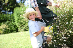 Little boy watering flowers Stock Photos
