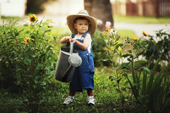 Little boy watering flowers stock photo