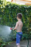 Little boy watering with hose Stock Images